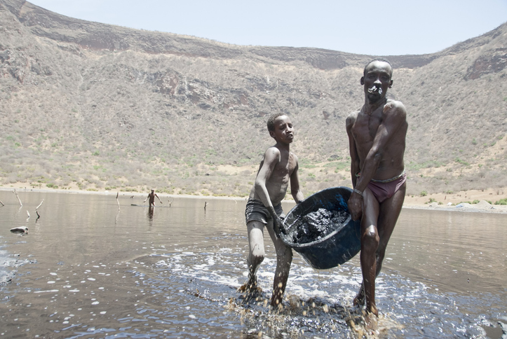 El Sod, Ethiopia - March 8th, 2012: Unidentified Borana boy helps his father to mine salt from the crater lake El Sod, Ethiopia on March 8, 2012.